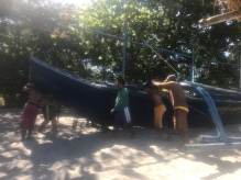 Locals rolling their boat to the water--Teamwork!